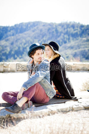 young couple wearing hats sitting looking