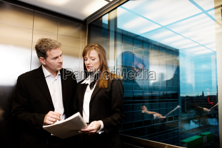 man and woman discussing a file