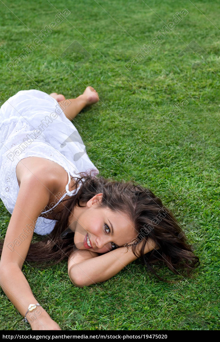 young, woman, lays, in, grass - 19475020