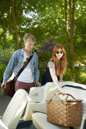 young couple putting picnic basket in