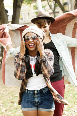young man chasing girlfriend with poncho