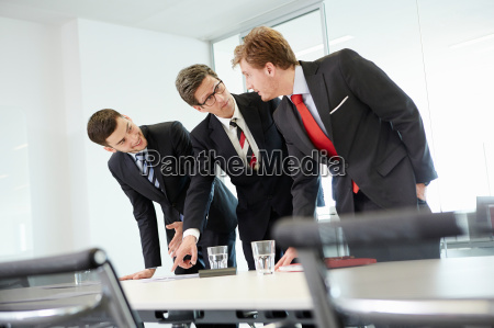 businessmen leaning over conference table pointing