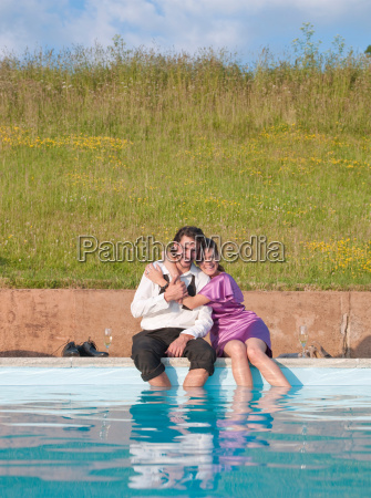 couple sat by swimming pool embraced