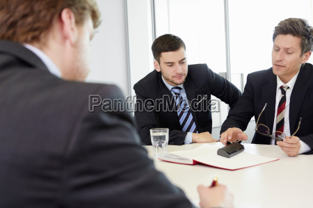 businessmen sitting around conference table having