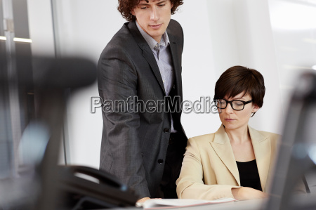businesswoman sitting at desk man looking