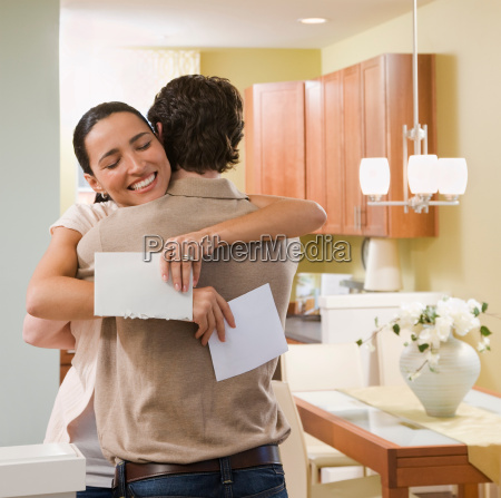 couple hugging after receiving a card