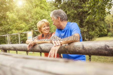 couple leaning on fence face to
