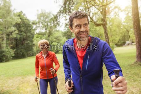 couple walking outdoors using walking poles