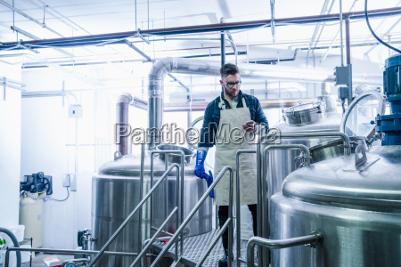 young man in brewery wearing apron