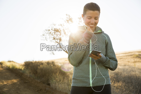 mature female runner on sunlit hill