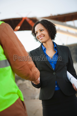 woman shaking hands with man on
