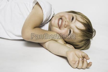 studio portrait of cute girl lying