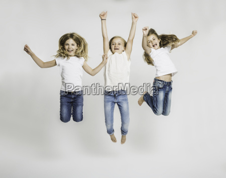 studio portrait of three girls jumping