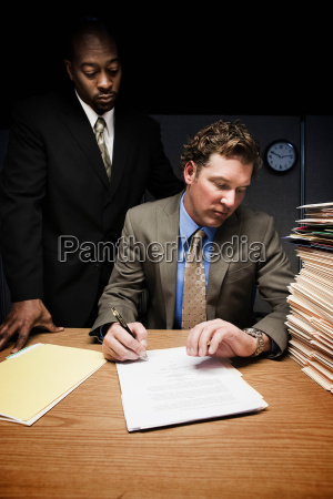 man at desk with man over