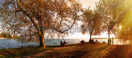 panoramablick auf touristen am sonnendurchfluteten zugersee