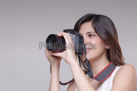 young woman taking photograph with digital