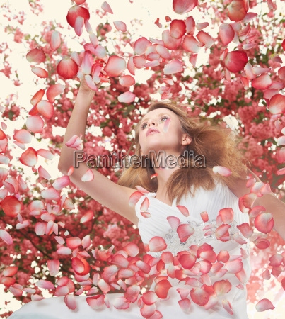 woman surrounded by flower petals