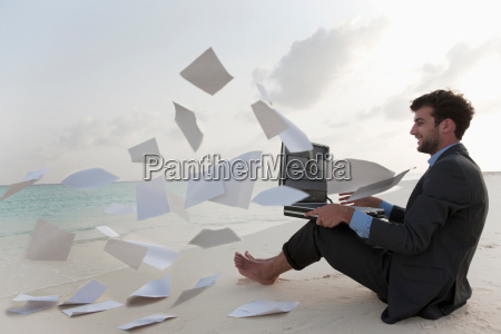 businessmans documents flying in wind