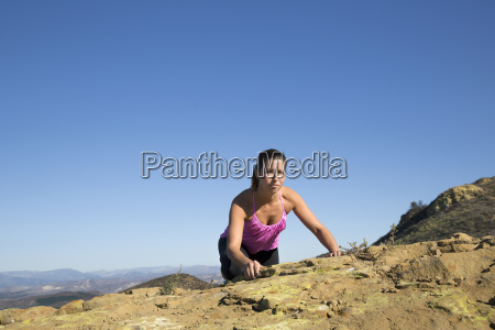 female runner clambering to top of