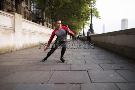 young man training along riverbank