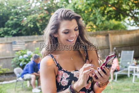 woman texting on smartphone at party