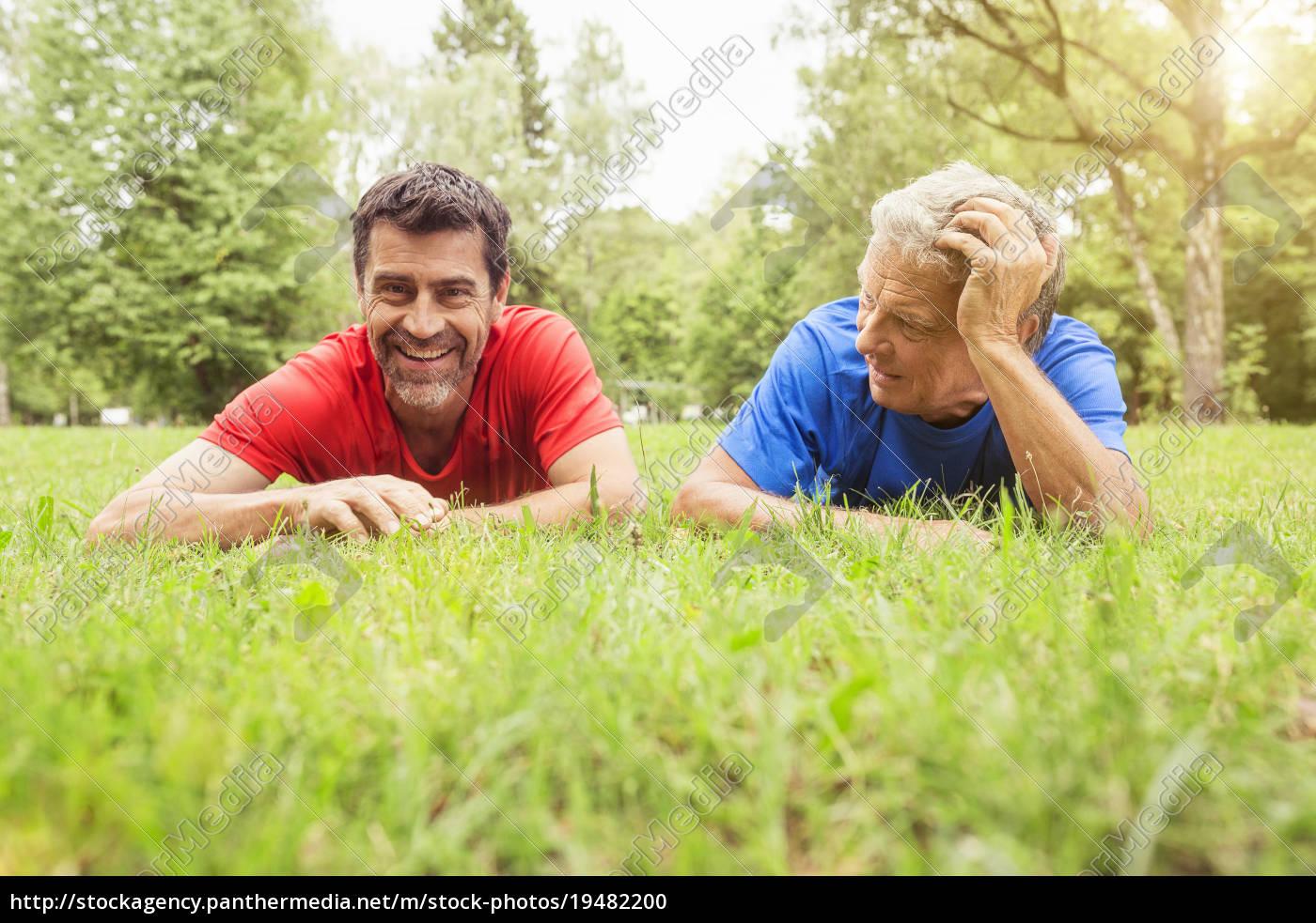 two, men, relaxing, on, grass, following - 19482200