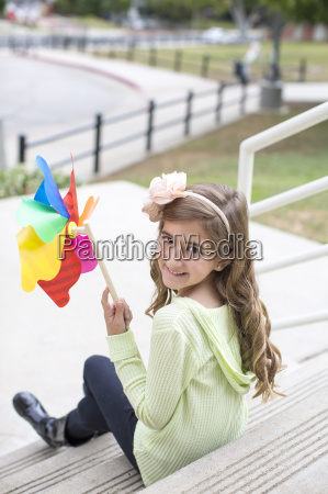 girl with paper windmill in park