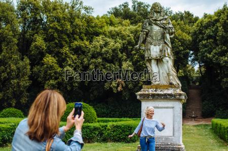 mature female friends taking smartphone photographs