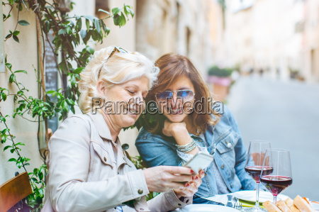 two mature female friends looking at