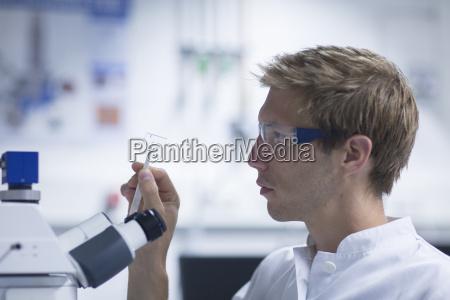 male scientist looking at microscope slide