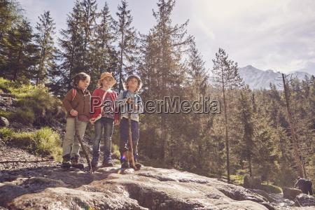 three children standing on rock in