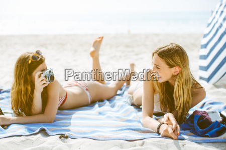 two young female friends taking photographs