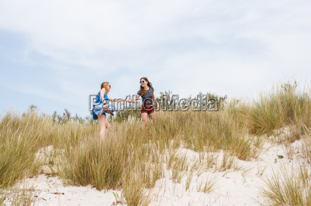 two young female friends running and