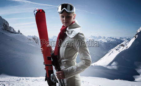 woman carrying skis on snowy mountain
