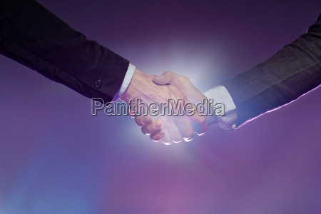 two men shaking hands light illuminating
