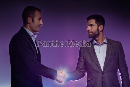 two men shaking hands light illuminating