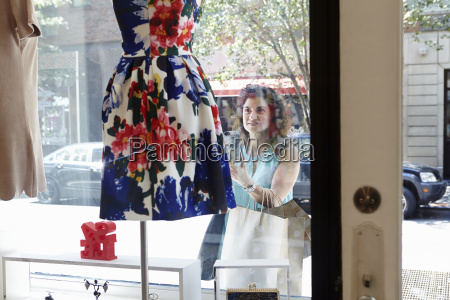 mature woman looking in window of