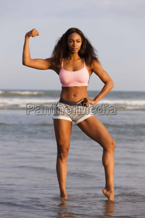 young woman on beach flexing muscles