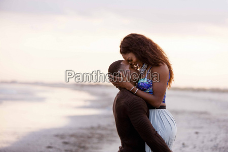 couple on beach hugging face to