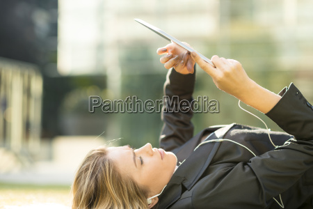 young city businesswoman lying outside office