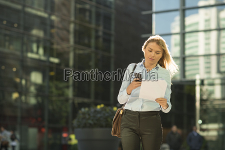 young city businesswoman reading paperwork outside