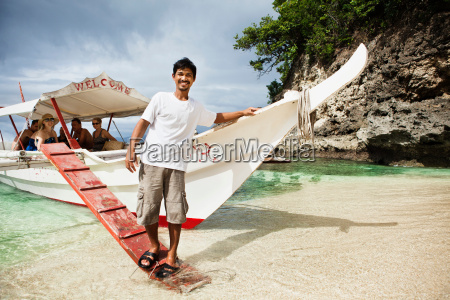 man with tour boat on tropical
