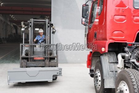 male factory worker driving forklift truck