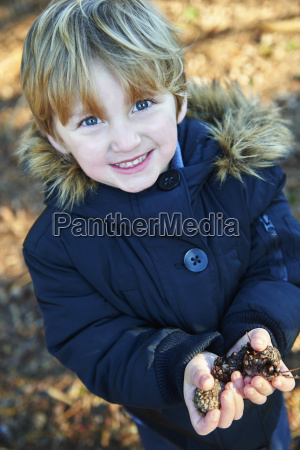 young boy holding pine cones in