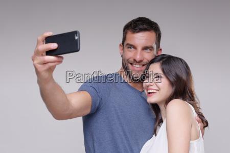 heterosexual couple taking self portrait using