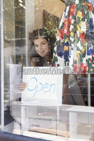 female business owner placing open sign