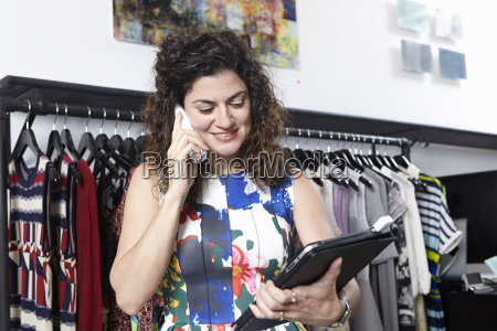 retail assistant in clothes shop using