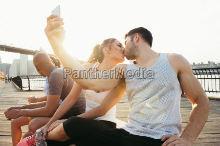 young adult running couple kissing for