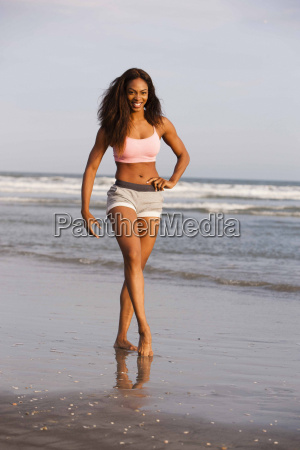 young woman walking along beach hand