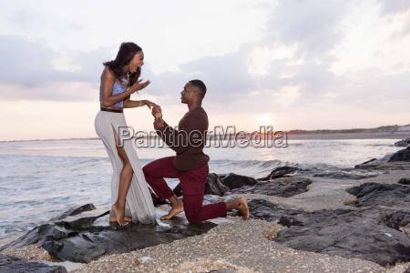 mid adult man kneeling on rocks